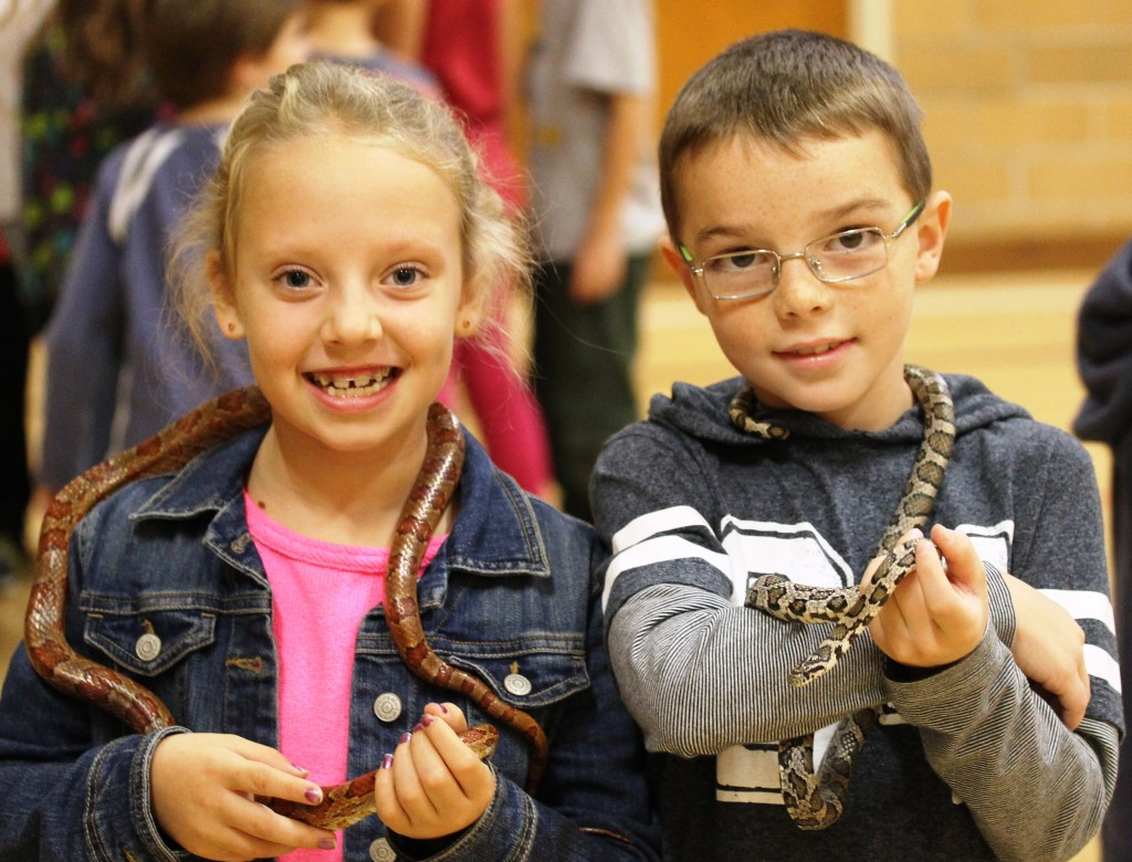 Boy and Girl holding snakes